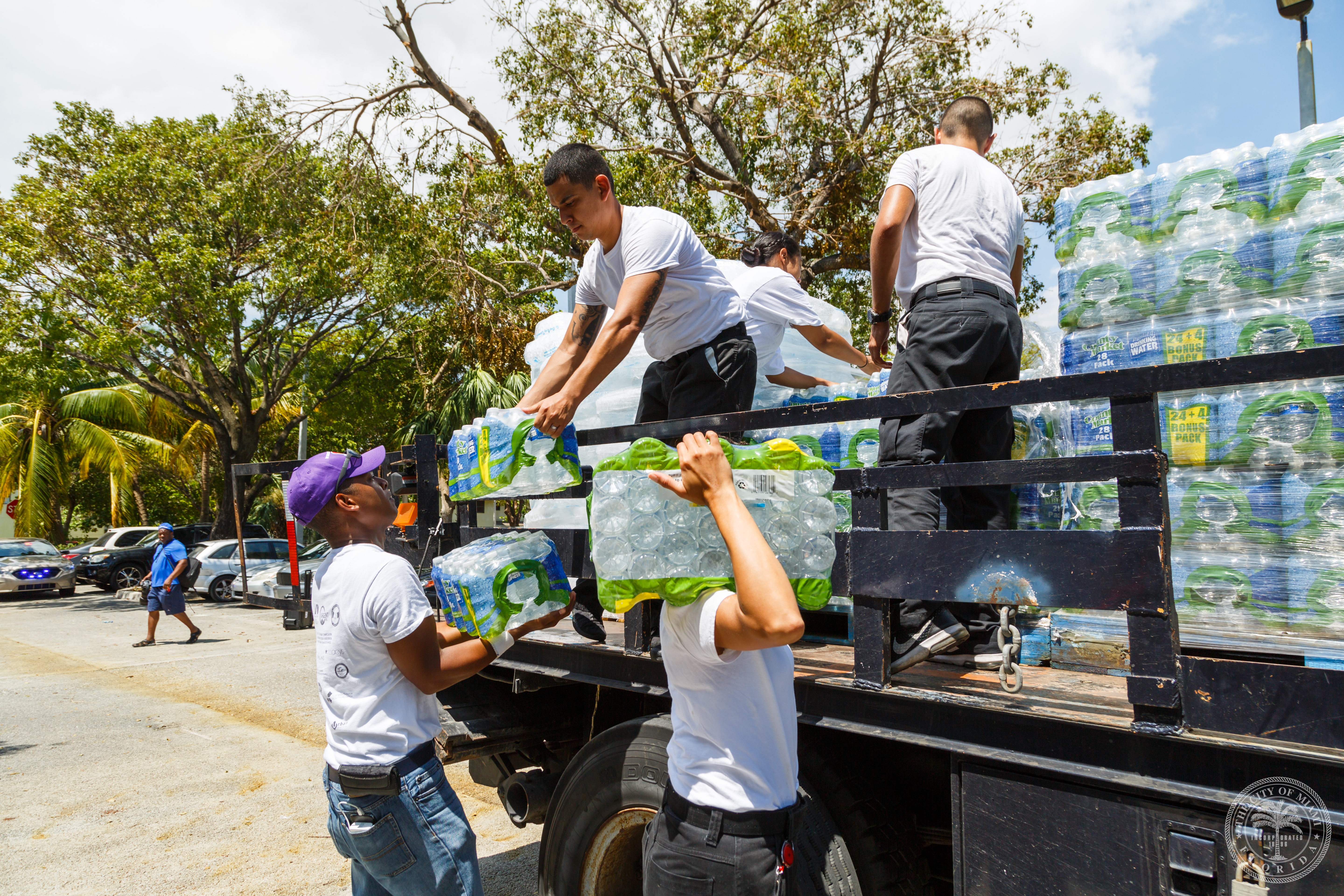 city staff unloading packages of water bottles off a truck
